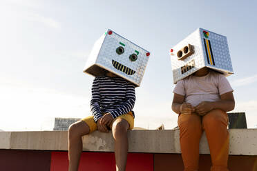 Friends wearing robot masks sitting on retaining wall against clear sky during sunny day - VABF03143
