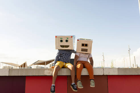 Friends wearing robot costumes sitting on retaining wall against clear sky during summer - VABF03146