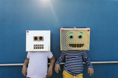 Friends wearing robot costumes made of boxes while standing against blue wall - VABF03149