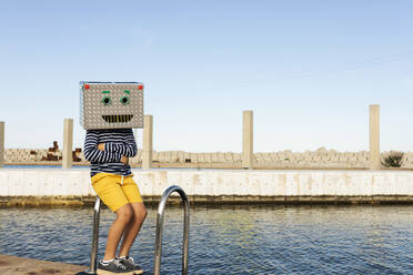Boy wearing robot mask made of box while sitting on railing by the water against clear sky - VABF03152