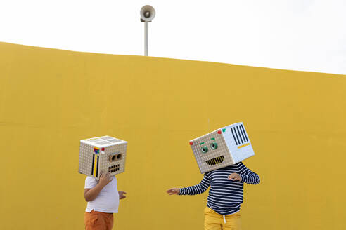 Friends wearing robot costumes standing against yellow wall - VABF03155