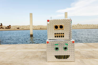 Robot masks made of boxes on footpath against water - VABF03158