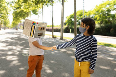 Boy in face mask giving handshake to friend wearing robot costume while standing on road - VABF03161