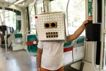 Boy wearing robot mask made of box standing in train - VABF03164