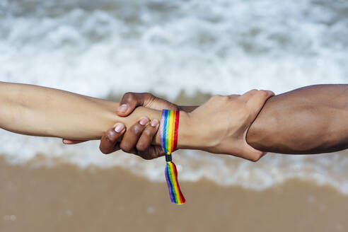 Close-up of couple holding hands over sea on sunny day - OCMF01480