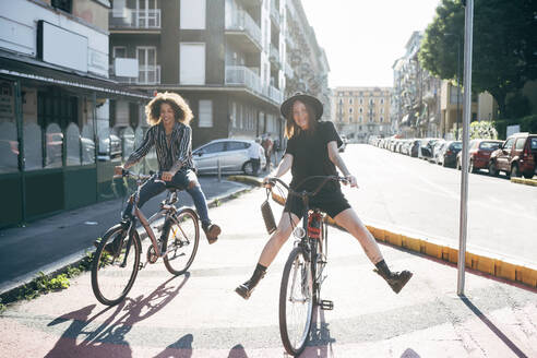 Happy couple riding bicycles on city street during sunny day - MEUF01550