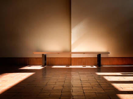 Interior shot of bench on stone floor in sunbeam against plain white wall - ADSF02971