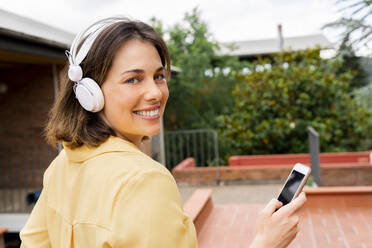 Young woman listening to music on terrace - AFVF06809