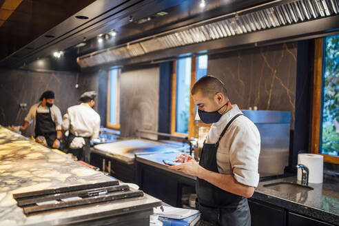 Chef wearing protective face mask using smartphone in restaurant kitchen - OCMF01508