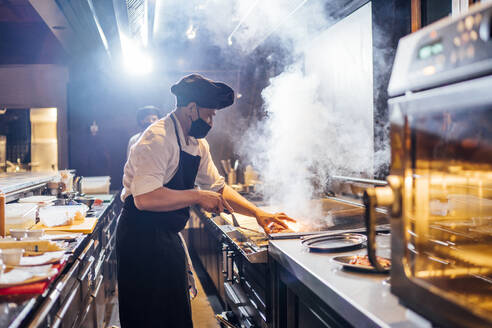 Chef wearing protective face mask preparing a dish in restaurant kitchen - OCMF01523