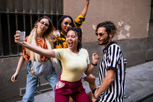 Group of young people in trendy outfits laughing and taking selfie while having fun on city street - ADSF03797