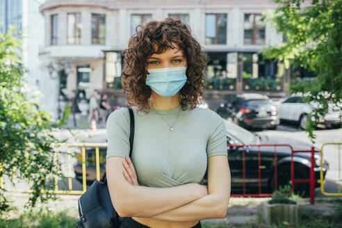 Brunette curly woman wearing protective mask in city - OYF00145