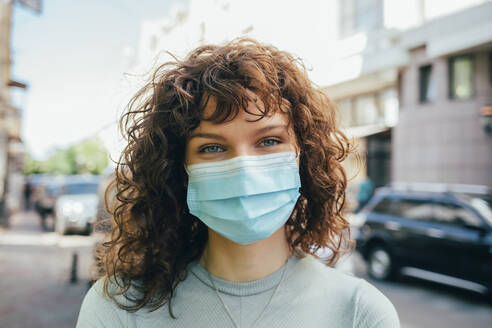 Brunette curly woman wearing protective mask in city - OYF00151