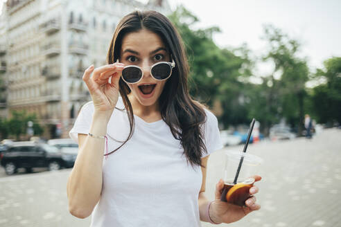 Surprised young woman with mouth open wearing sunglasses while standing on city street - OYF00169