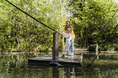 Mother and daughter standing on wooden raft over lake in forest - DIGF12760