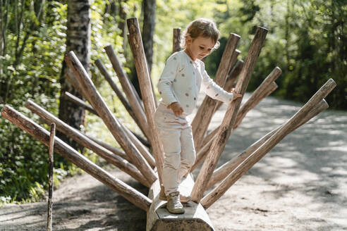 Cute girl standing on wood in forest - DIGF12763