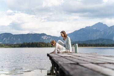 Mother with daughter sitting on jetty over lake against sky - DIGF12766