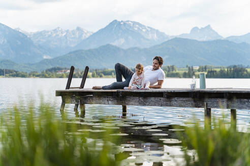 Father with daughter relaxing on jetty over lake against mountains - DIGF12772