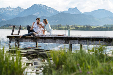Parents with daughter sitting on jetty over lake against mountains - DIGF12775