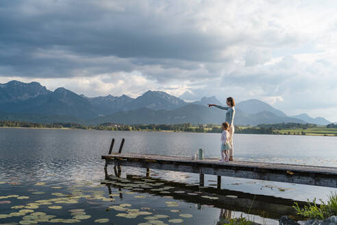 Mother pointing while standing with daughter on jetty over lake against cloudy sky - DIGF12778