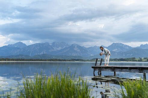 Mother carrying daughter while standing on jetty over lake against cloudy sky - DIGF12781