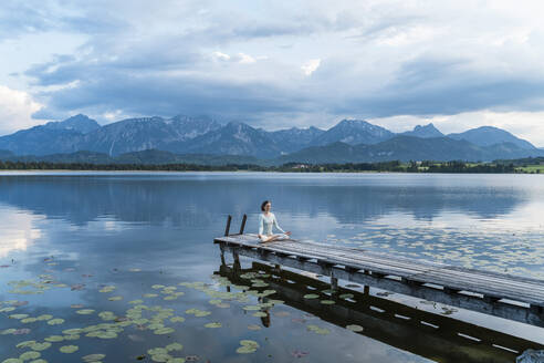 Woman meditating while sitting on jetty over lake against mountains - DIGF12787