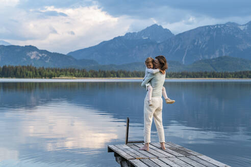 Happy mother carrying daughter while standing on jetty over lake against mountain - DIGF12790