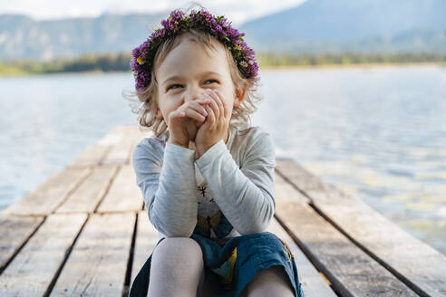 Close-up of cute girl wearing tiara laughing while sitting on jetty against lake - DIGF12793