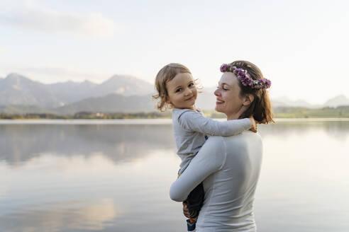 Smiling mother wearing tiara carrying daughter while standing against lake at sunset - DIGF12796