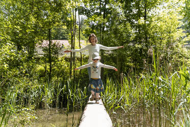 Mother and daughter with arms outstretched walking on footbridge against trees in forest - DIGF12799