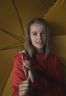Close-up of woman with blond hair holding yellow umbrella standing in city - HPSF00036