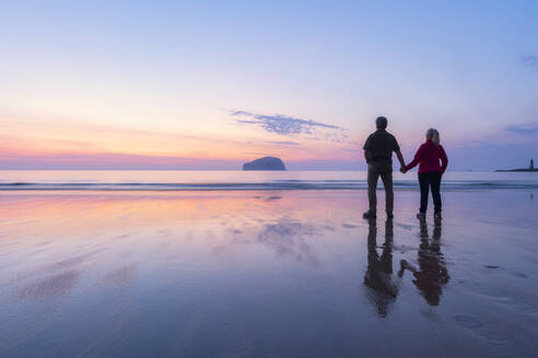 Couple looking at sea while standing on Seacliff Beach, North Berwick, Scotland during sunset - SMAF01936
