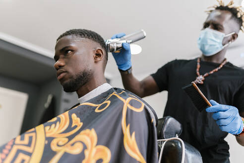 Young man wearing mask and gloves cutting customer's hair with razor in salon - EGAF00564