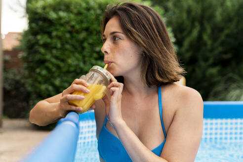 Beautiful woman drinking orange juice in inflatable swimming pool at yard - AFVF06817