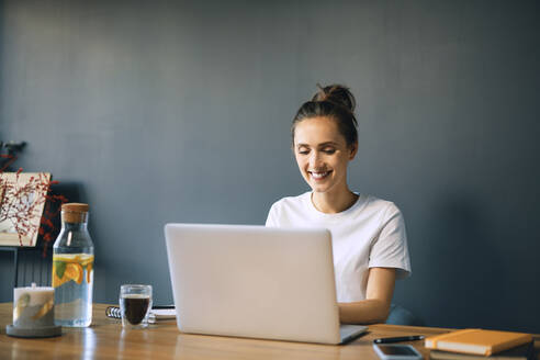 Smiling businesswoman using laptop on desk against wall in home office - BSZF01573