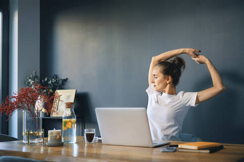 Tired businesswoman stretching arms while sitting at desk in home office - BSZF01576