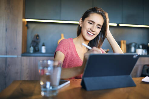 Smiling businesswoman using digital tablet on desk in home office - BSZF01603
