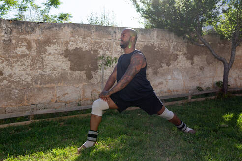 Bald mature man exercising on grassy land against wall in yard - JPTF00567