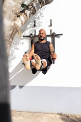 Bald mature man exercising on equipment against wall in yard during sunny day - JPTF00570