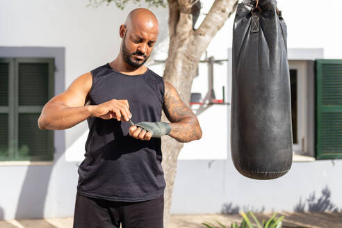 Bald mature man tying bandage on hand while standing by punching bag in yard - JPTF00573