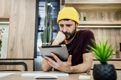 Businessman using digital tablet at desk in modern office - RCPF00266