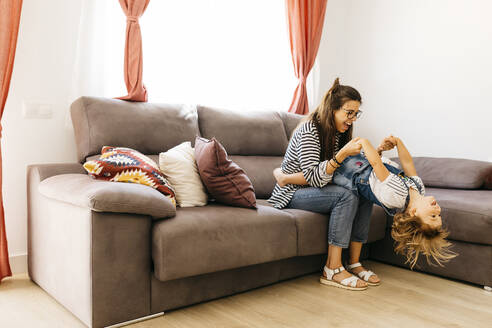 Happy mother and daughter playing on sofa at home - JRFF04598