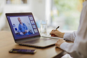 Woman video conferencing with doctor at laptop - CAIF28736