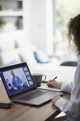 Woman video conferencing with doctor on laptop screen - CAIF28757