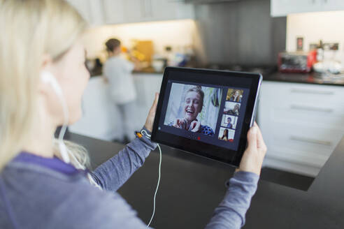 Woman video chatting with friends on digital tablet - CAIF29100