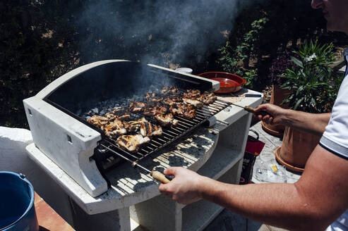 Young man cooking meat on barbecue grill in yard - JCMF01054