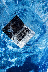 High angle view of computer falling in swimming pool - JCMF01063