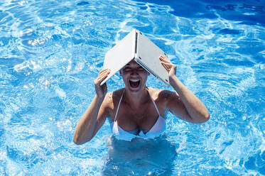 Cheerful woman holding laptop on head while swimming in pool - JCMF01066