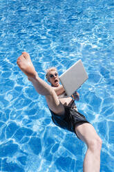 Shirtless young man holding laptop falling in swimming pool - JCMF01069