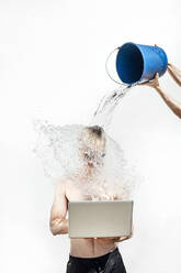 Hands of woman pouring water with bucket on shirtless young man using laptop against wall - JCMF01075